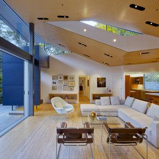 Imagen de salón abierto, minimalista, de tamaño medio, con televisor retractable, paredes blancas y suelo de madera clara