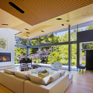 Diseño de salón con rincón musical cerrado, moderno, de tamaño medio, sin televisor, con chimenea tradicional, paredes blancas, suelo de madera clara y marco de chimenea de yeso