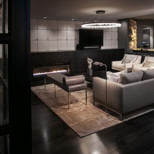 Ejemplo de salón con barra de bar cerrado, moderno, de tamaño medio, con paredes blancas, suelo de madera pintada, chimenea tradicional, marco de chimenea de metal y televisor colgado en la pared