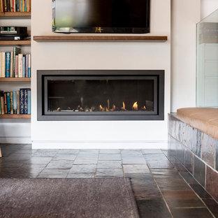 Idee per un soggiorno scandinavo di medie dimensioni e aperto con pareti bianche, pavimento in ardesia, camino classico, cornice del camino in intonaco, TV a parete e pavimento marrone