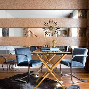 Imagen de biblioteca en casa contemporánea, pequeña, sin chimenea, con paredes multicolor y suelo de madera en tonos medios