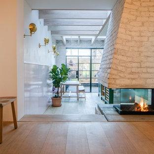 Foto de salón abierto, nórdico, sin televisor, con paredes rosas, suelo de madera en tonos medios, chimenea de doble cara y marco de chimenea de ladrillo