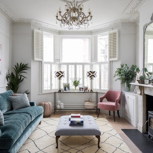 Scandi formal living room in London with white walls, light hardwood flooring, a wood burning stove, no tv and beige floors.