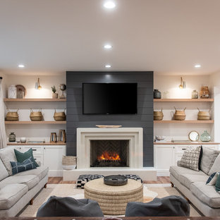 This is an example of a country enclosed living room in Salt Lake City with white walls, medium hardwood floors, a standard fireplace and brown floor.