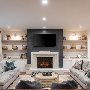 Bild på ett lantligt separat vardagsrum, med vita väggar, mellanmörkt trägolv, en standard öppen spis och brunt golv