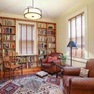 Idee per un piccolo soggiorno classico chiuso con libreria, pareti gialle e pavimento in legno massello medio