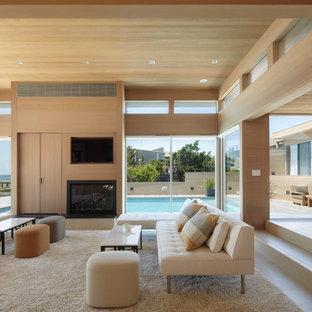 Imagen de salón abierto, costero, grande, con paredes beige, chimenea tradicional, pared multimedia, suelo de baldosas de porcelana, marco de chimenea de madera y suelo beige