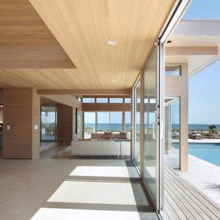 ニューヨークの大きいビーチスタイルのおしゃれなLDK (ベージュの壁、磁器タイルの床、標準型暖炉、木材の暖炉まわり、埋込式メディアウォール、ベージュの床) の写真