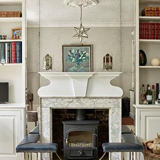 Modelo de salón clásico renovado con paredes beige, suelo de madera oscura, estufa de leña, marco de chimenea de piedra y suelo negro