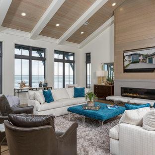 マイアミの中サイズのビーチスタイルのおしゃれな独立型リビング (フォーマル、白い壁、淡色無垢フローリング、標準型暖炉、コンクリートの暖炉まわり、壁掛け型テレビ) の写真