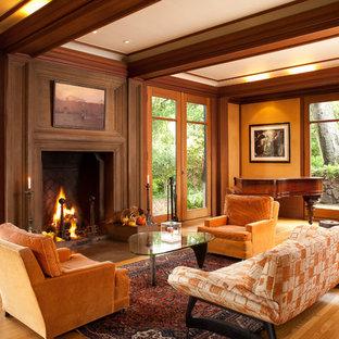 Idee per un soggiorno stile americano con pareti arancioni, pavimento in legno massello medio, cornice del camino in legno e pavimento arancione
