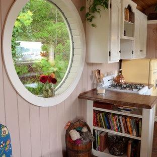 Esempio di un piccolo soggiorno stile americano aperto con pareti beige, pavimento in legno massello medio e nessuna TV