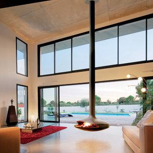 Diseño de salón para visitas abierto, minimalista, grande, sin televisor, con paredes blancas, suelo de cemento, chimeneas suspendidas, suelo gris y marco de chimenea de yeso