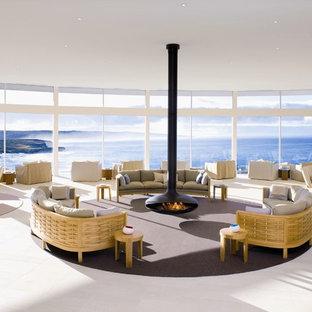 デヴォンの巨大なコンテンポラリースタイルのおしゃれなLDK (吊り下げ式暖炉、セラミックタイルの床) の写真