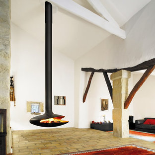 Living room - rustic brick floor living room idea in Devon with a hanging fireplace