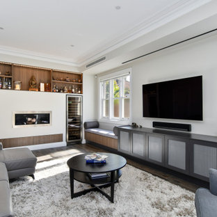 Inspiration for a large contemporary open concept living room in Sydney with a home bar, grey walls, dark hardwood floors, a ribbon fireplace, a wall-mounted tv and brown floor.