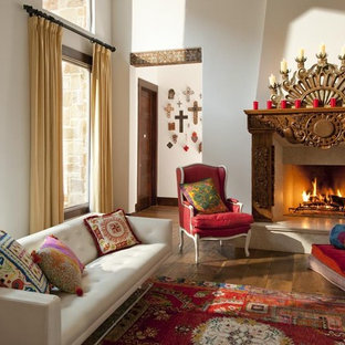 Example of a southwest open concept medium tone wood floor living room design in San Diego with white walls and a standard fireplace
