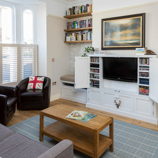 Inspiration for a medium sized traditional enclosed living room in London with beige walls, light hardwood flooring, a concealed tv and brown floors.