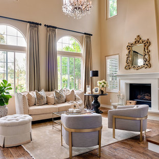 Example of a classic dark wood floor and brown floor living room design in Los Angeles with beige walls and a standard fireplace