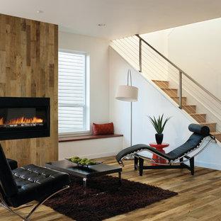 Modern inredning av ett stort allrum med öppen planlösning, med flerfärgade väggar, mellanmörkt trägolv, en standard öppen spis och en spiselkrans i trä