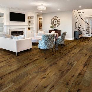 Idee per un grande soggiorno moderno aperto con pareti bianche, pavimento in legno massello medio, camino classico e cornice del camino in intonaco