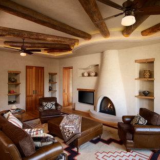 トロントのサンタフェスタイルのおしゃれな独立型リビング (ベージュの壁、標準型暖炉、コンクリートの暖炉まわり、埋込式メディアウォール) の写真