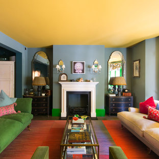 This is an example of a medium sized bohemian enclosed living room in London with green walls, carpet, a standard fireplace, a stone fireplace surround and beige floors.