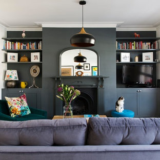 Inspiration for a small transitional medium tone wood floor and brown floor living room remodel in London with gray walls, a standard fireplace and a wall-mounted tv