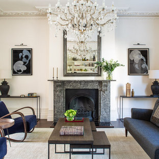 Design ideas for a traditional enclosed living room in London with white walls, dark hardwood flooring, a standard fireplace and brown floors.