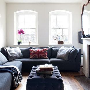 Foto de salón cerrado, ecléctico, pequeño, con paredes blancas, suelo de madera en tonos medios y chimenea tradicional