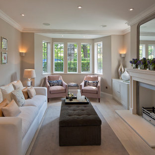 Traditional enclosed living room in London with beige walls and a standard fireplace.