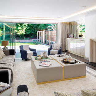 Photo of a large classic formal enclosed living room in London with white walls, dark hardwood flooring, a standard fireplace, a stone fireplace surround and a concealed tv.