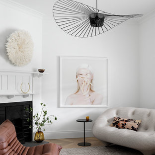 Inspiration for a contemporary formal enclosed living room in Melbourne with white walls, medium hardwood floors, a corner fireplace, a wood fireplace surround, no tv and brown floor.