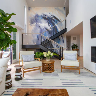 Example of a beach style open concept light wood floor and beige floor living room design in New York with white walls, a ribbon fireplace and a wall-mounted tv