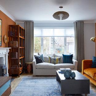 Diseño de salón clásico renovado, de tamaño medio, con parades naranjas, suelo de madera clara, estufa de leña, marco de chimenea de ladrillo, televisor independiente y suelo beige