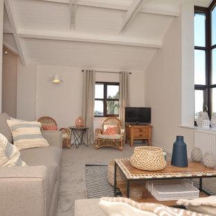 デヴォンの中サイズのビーチスタイルのおしゃれなLDK (グレーの壁、カーペット敷き、据え置き型テレビ、グレーの床) の写真