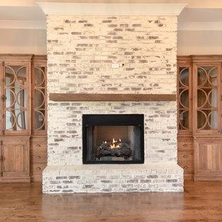 Aménagement d'un grand salon craftsman ouvert avec un mur gris, un sol en bois foncé, une cheminée standard, un manteau de cheminée en brique et aucun téléviseur.