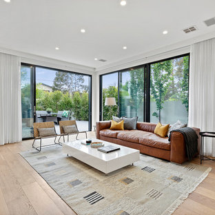 Large contemporary open concept living room in Melbourne with white walls, medium hardwood floors, no fireplace and brown floor.