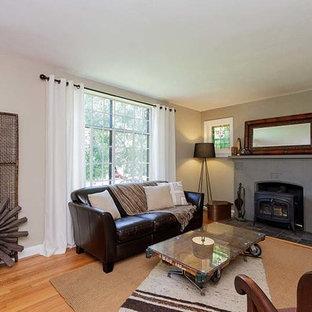 Idee per un piccolo soggiorno stile americano con pareti beige, parquet chiaro, stufa a legna, cornice del camino in pietra e nessuna TV