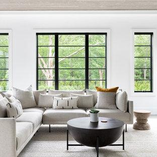 ニューヨークの大きいビーチスタイルのおしゃれなLDK (白い壁、濃色無垢フローリング、吊り下げ式暖炉、石材の暖炉まわり、据え置き型テレビ、グレーの床) の写真