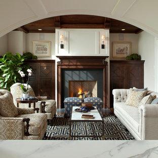 Ejemplo de salón para visitas tradicional, de tamaño medio, sin televisor, con paredes beige, suelo de madera oscura, chimenea tradicional y marco de chimenea de piedra
