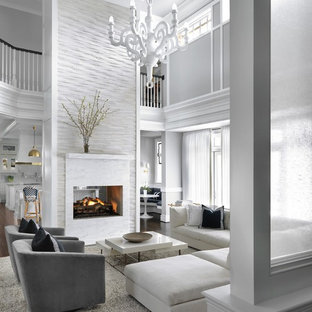 Inspiration for a large transitional open concept dark wood floor and brown floor living room remodel in St Louis with gray walls, a two-sided fireplace and a stone fireplace