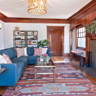 Modelo de salón de estilo americano con suelo de madera en tonos medios, chimenea tradicional y marco de chimenea de baldosas y/o azulejos