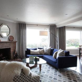 Modelo de salón abierto, moderno, pequeño, con paredes grises, suelo de madera en tonos medios, chimenea de esquina, marco de chimenea de ladrillo y televisor colgado en la pared