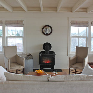 Country living room photo in Portland Maine with white walls and a wood stove