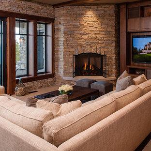 他の地域の大きいトラディショナルスタイルのおしゃれなLDK (コーナー設置型暖炉、石材の暖炉まわり、埋込式メディアウォール、マルチカラーの壁、ベージュの床) の写真