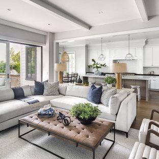 Неиссякаемый источник вдохновения для домашнего уюта: большая открытая гостиная комната в стиле современная классика с серыми стенами, светлым паркетным полом, коричневым полом, стандартным камином, фасадом камина из дерева, телевизором на стене и балками на потолке