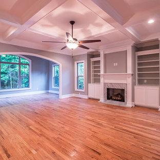 Réalisation d'un grand salon tradition ouvert avec une salle de réception, un mur gris, un sol en bois clair, une cheminée standard, un manteau de cheminée en pierre, aucun téléviseur et un sol marron.