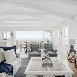 This is an example of a large beach style open concept living room in Brisbane with white walls, a wall-mounted tv and beige floor.