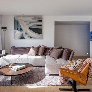 Ejemplo de salón para visitas abierto, minimalista, pequeño, con paredes blancas, suelo de madera clara, chimeneas suspendidas, televisor independiente y suelo beige